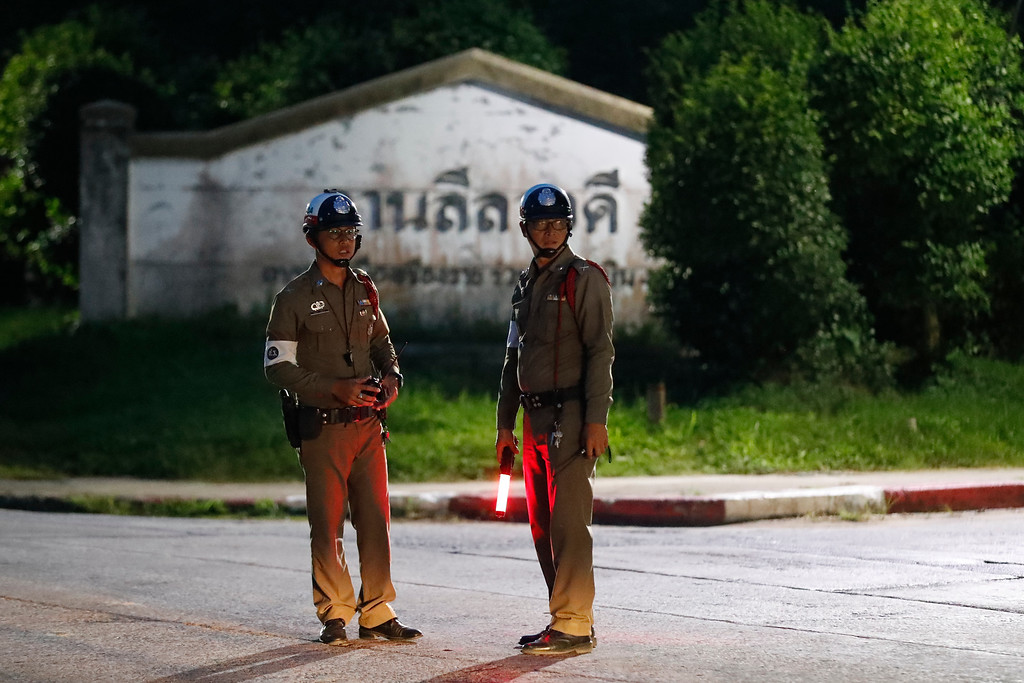 . Police man guard a junction for an ambulance believed to be carrying one of the rescued boys from the flooded cave, in the Mae Sai district of Chiang Rai province, northern Thailand, Monday, July 9, 2018. (AP Photo/Vincent Thian)