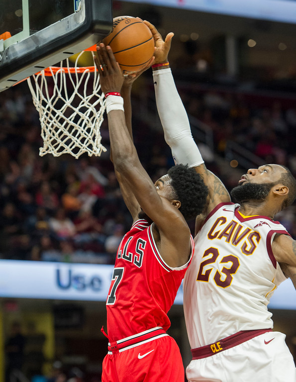 . Cleveland Cavaliers\' LeBron James (23) blocks a shot by Chicago Bulls\' Justin Holiday (7) during the second half of an NBA preseason basketball game in Cleveland, Tuesday, Oct. 10, 2017. The Bulls won 108-94. (AP Photo/Phil Long)
