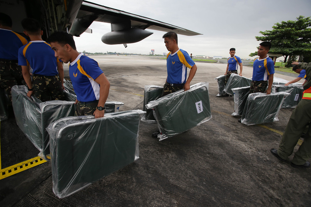 . Members of the Philippine Air Force carry cots on a C-130 military plane as they prepare to fly to Bohol island at Villamor Air Base in Pasay, south of Manila, Philippines on Thursday, Oct. 17, 2013. (AP Photo/Aaron Favila)