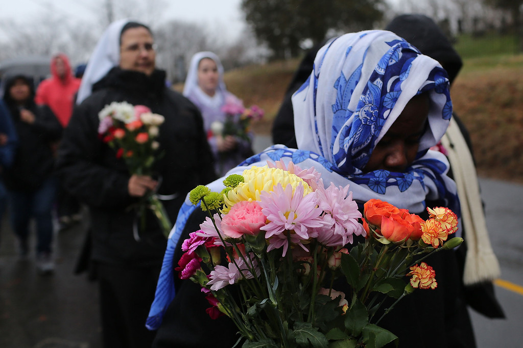 . NEWTOWN, CT - DECEMBER 16:  Members of Sisters of Christian Charity walk to lay flowers in front of the Sandy Hook School December 16, 2012 in Newtown, Connecticut. Twenty-six people were shot dead, including twenty children, after a gunman identified as Adam Lanza opened fire at Sandy Hook Elementary School. Lanza also reportedly had committed suicide at the scene. A 28th person, believed to be Nancy Lanza, found dead in a house in town, was also believed to have been shot by Adam Lanza.  (Photo by Spencer Platt/Getty Images)