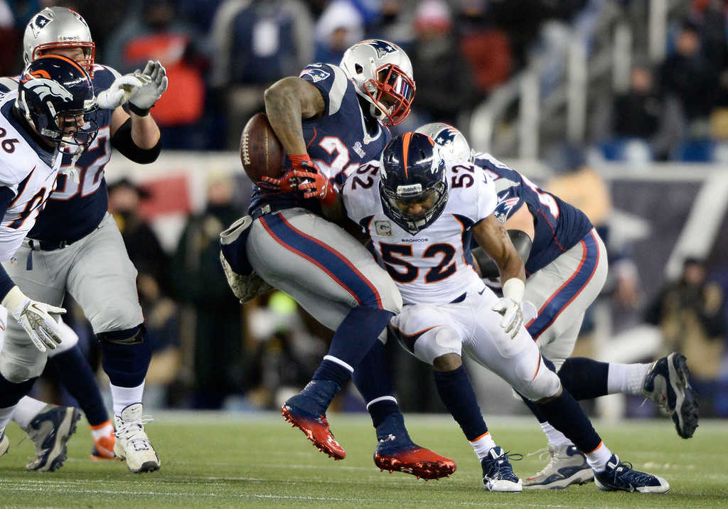 . Denver Broncos middle linebacker Wesley Woodyard (52) hits New England Patriots running back Stevan Ridley (22) on the ball and forces a fumble during the first quarter November 24, 2013 at Gillette Stadium. The fumble was picked up by Denver Broncos outside linebacker Von Miller (58) and ran it for a 60 Yard touchdown. (Photo by John Leyba/The Denver Post)