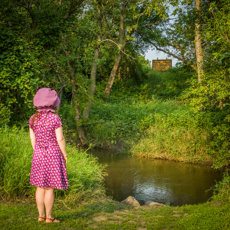 A woman wearing a bonnet looks across Plum Creek and up a hill to a sign that marks the location of the Ingalls dugout house.