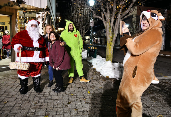 12/6/2019 Mike Orazzi | StaffrFriends Patty Justs and Lynn DiCristofaro pose with Santa and the Grinch as a reindeer snaps a photograph during Southington's White Christmas in the Community on the town green on Friday evening.