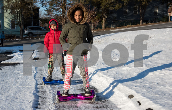 12/26/17 Wesley Bunnell | Staff Baryelia Sierra, age 8, leads the way through a snowy parking lot on Tuesday afternoon as friend Yendrial Colon, age 8, follows as they both ride their new hover boards they received for Christmas.