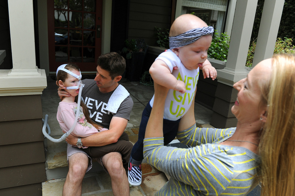 . Bill Strong sits with his daughter Gwendolyn as Victoria Strong lifts Eleanora in front of their Santa Barbara home. Gwendolyn was born with spinal muscular atrophy. (Photo by Michael Owen Baker/Los Angeles Daily News)