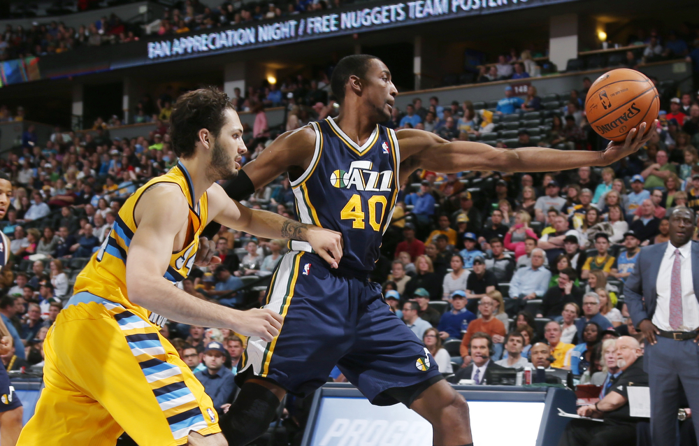 . Utah Jazz forward Jeremy Evans, right, reaches out to pull in a loose ball as Denver Nuggets guard Evan Fournier, of France, covers in the first quarter of an NBA basketball game in Denver on Saturday, April 12, 2014. (AP Photo/David Zalubowski)