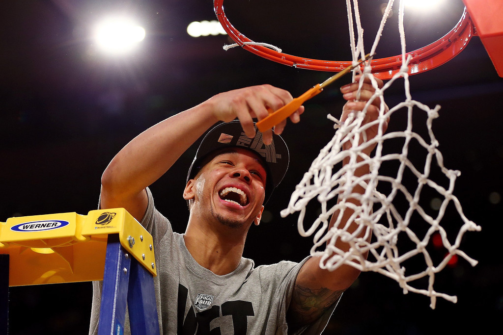 . Shabazz Napier #13 of the Connecticut Huskies cuts down the net after defeating the Michigan State Spartans to win the East Regional Final of the 2014 NCAA Men\'s Basketball Tournament at Madison Square Garden on March 30, 2014 in New York City.  (Photo by Elsa/Getty Images)