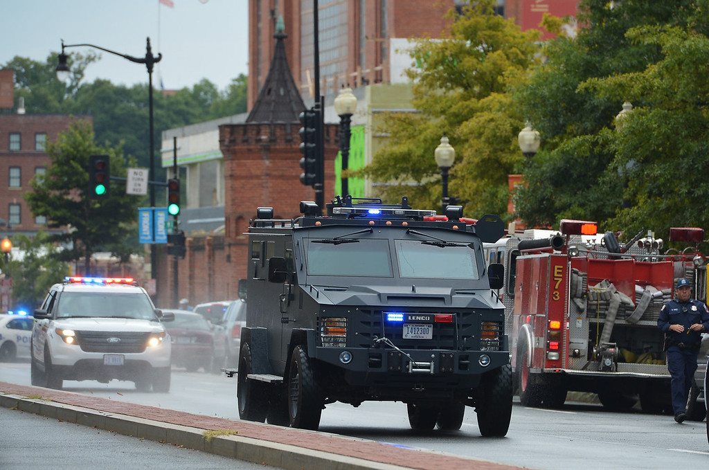 """. An armored personnel carrier speeds down M Street, SE away from the Washington Navy Yard on September 16, 2013 in Washington, DC.  At least one unidentified gunman opened fire at the US Navy Yard in Washington on Monday and was at large after killing \""""multiple\"""" victims and wounding several more, officials said. Police and FBI agents descended on the area in force as helicopters swarmed overhead, amid reports a shooter was armed with an assault rifle and was holed up at the complex. \""""We believe there were multiple deaths,\"""" a US defense official, speaking on condition of anonymity, told AFP. The precise death toll remained unclear, the official said. A Washington DC police officer and another law enforcement officer had been shot while the gunman had allegedly barricaded himself in a room in a headquarters building, media reported.   MANDEL NGAN/AFP/Getty Images"""