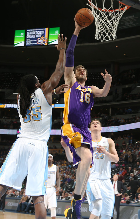 . Los Angeles Lakers center Pau Gasol, center, of Spain, drives the lane for a shot as Denver Nuggets forward Kenneth Faried, left, and center Timofey Mozgov, of Russia, cover in the first quarter of an NBA basketball game in Denver on Friday, March 7, 2014. (AP Photo/David Zalubowski)