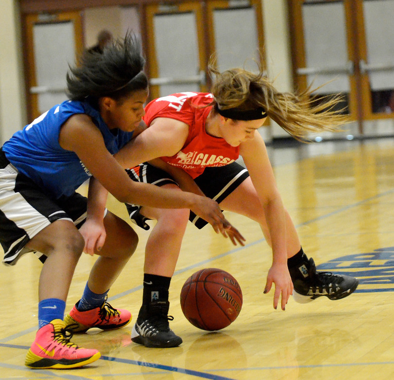 . Jeff Forman/JForman@News-Herald.com Mikah Aldridge, Blue, and Lyunsey Englebrecht reach for a loose ball during the 36th News-Herald Classic March 29 at Lakeland Community College.