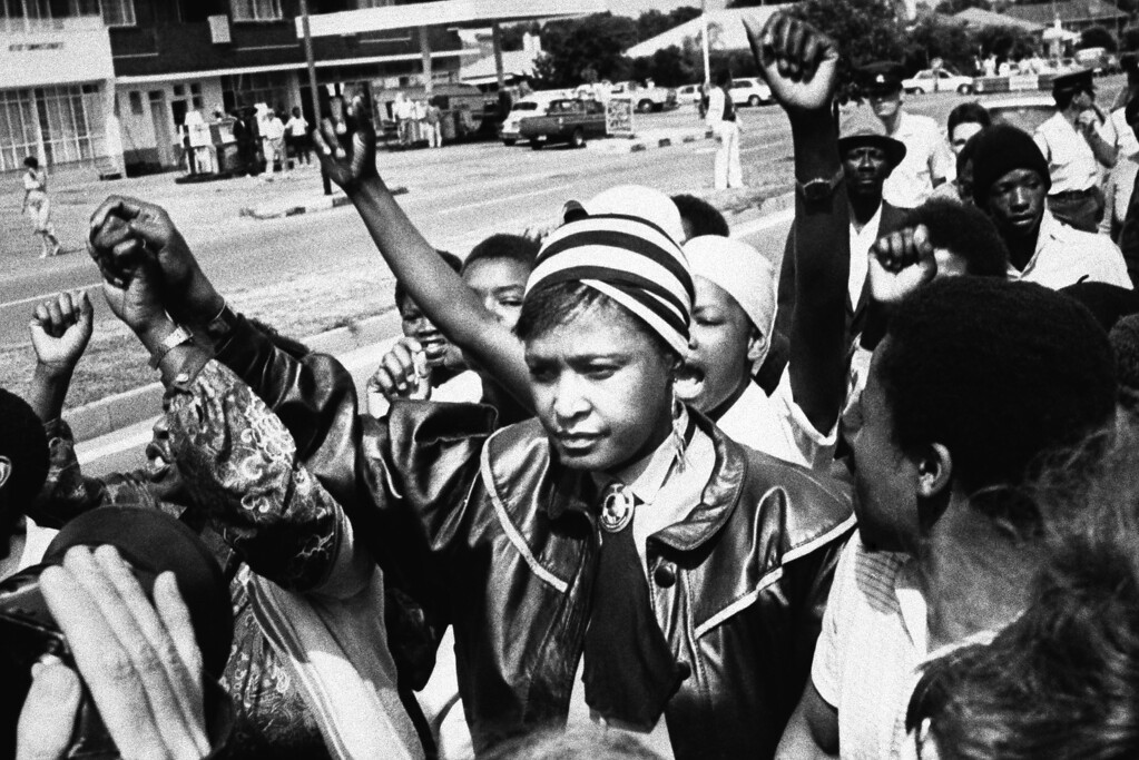 """. Black activist Winnie Mandela is cheered by supporters after appearing in the Krugersdorp Magistrate\'s court, West of Johannesburg on Jan. 22, 1986 in Krugersdorp, South Africa. In connection with her arrest for flouting a banning order which prevents her from living in her Soweto home. Mrs. Mandela was not asked to plead and her case was postponed to February 19. 1986(AP Photo) \""""South Africa Out\"""""""