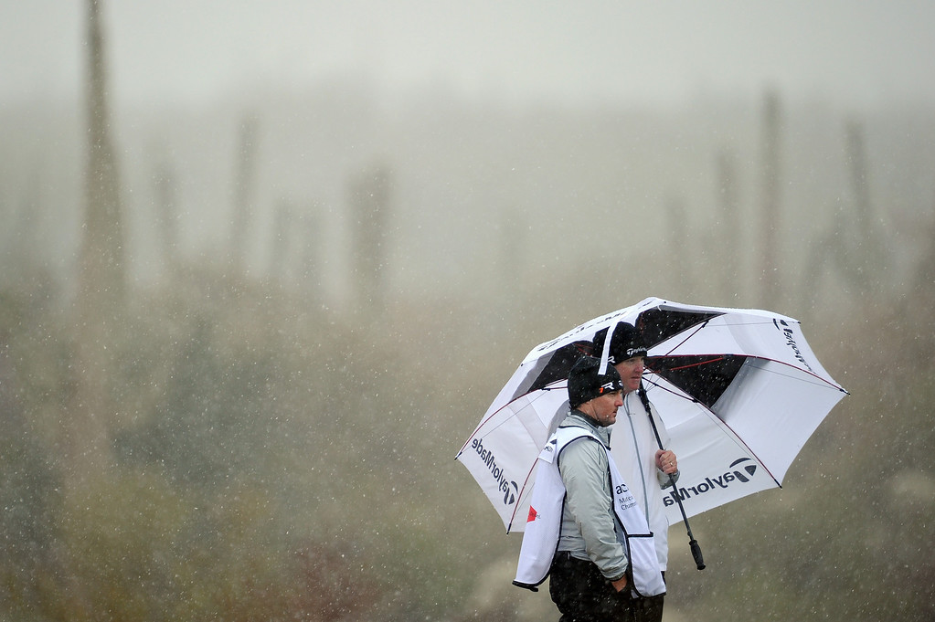 . MARANA, AZ - FEBRUARY 20:  Marcus Fraser of Australia stands under an umbrella with his caddie as snow and rain fall during the first round of the World Golf Championships - Accenture Match Play at the Golf Club at Dove Mountain on February 20, 2013 in Marana, Arizona.  (Photo by Stuart Franklin/Getty Images)