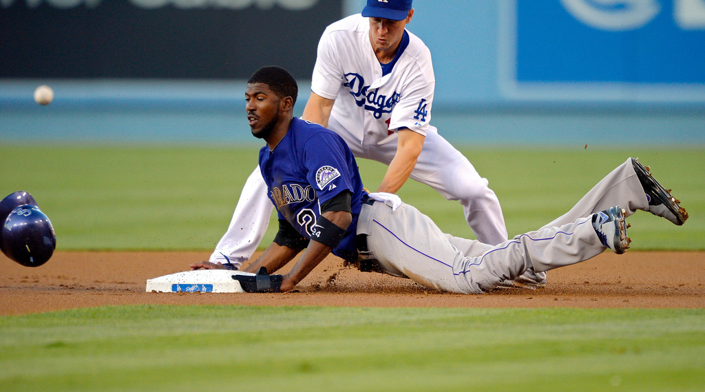 . Colorado Rockies\' Dexter Fowler, below, steals second as Los Angeles Dodgers second baseman Mark Ellis loses the ball during the first inning of their baseball game, Friday, July 12, 2013, in Los Angeles.  (AP Photo/Mark J. Terrill)