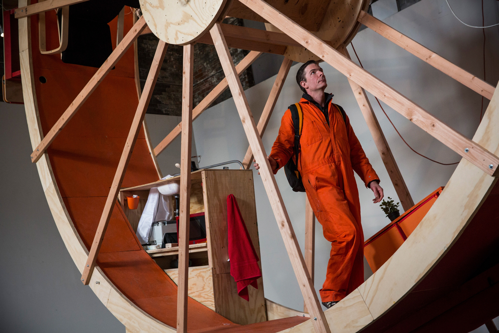 """. Alex Schweder, a professor, designer and artist, lives in the art installation piece titled, \""""In Orbit\"""" on March 5, 2014 in the Williamsburg neighborhood of the Brooklyn Borough of New York City. Schweder designed and constructed the space with Ward Shelley, who lives on the top of the hamster wheel-like environment; they are in the midst of living in the wheel for ten days. The space was designed complete with beds, desks, a kitchen and bathroom and chair for relaxing.  (Photo by Andrew Burton/Getty Images)"""