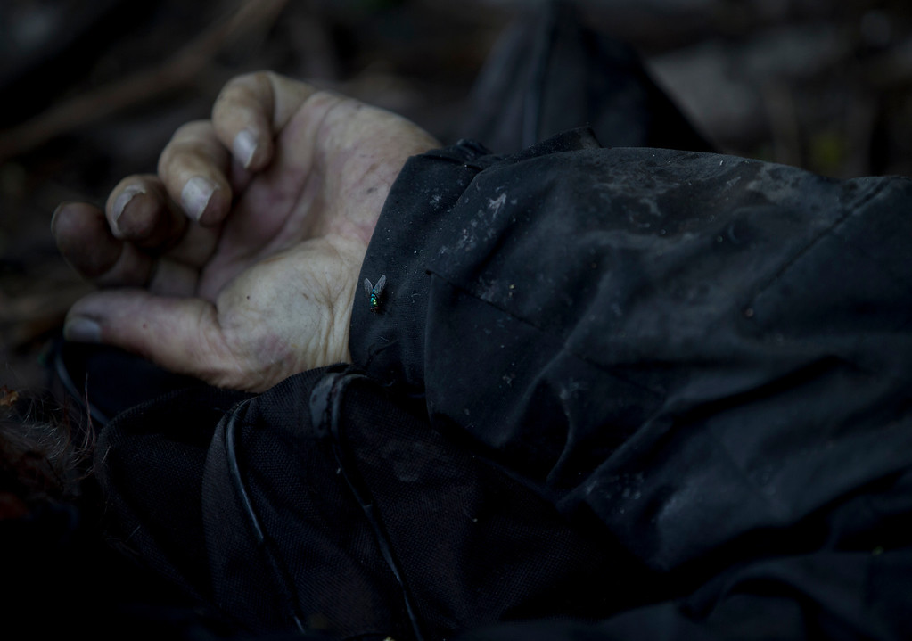 . The body of a man, who was killed during fighting, lies on the ground in the village of Karlivka, west of Donetsk, Ukraine, Friday, May 23, 2014.  (AP Photo/Vadim Ghirda)