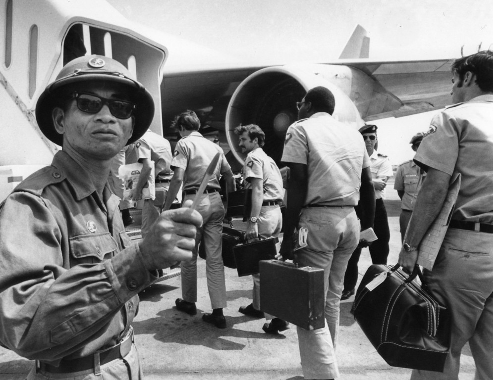 . A Viet Cong observer of the Four Party Joint Military Commission counts U.S. troops as they prepare to board jet aircraft at Saigonís Tan Son Nhut airport, March 28, 1973.  Nineteen planeloads of U.S. personnel left Vietnam as the withdrawal of American troops drew to a close according to the provisions of the Paris Accords. (AP Photo/Neal Ulevich)