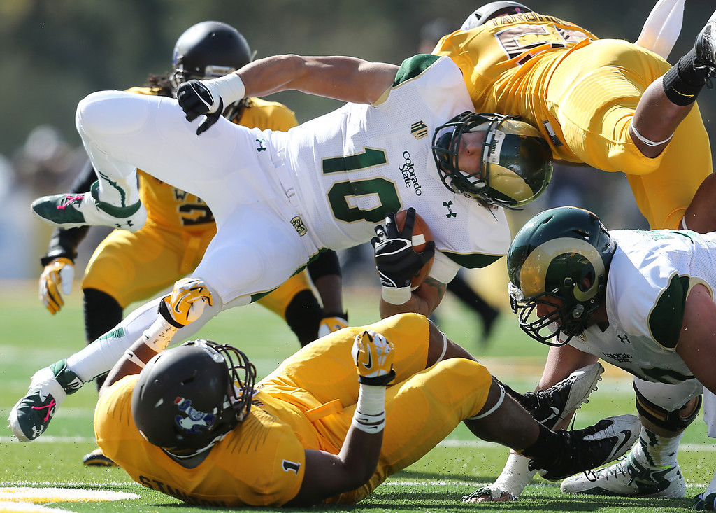 . Colorado State\'s Crockett Gillmore is tackled by Wyoming defenders during the first quarter  of an NCAA college football game Saturday, Oct. 19, 2013, in Laramie, Wyo. (AP Photo/The Wyoming Tribune Eagle, Michael Smith)