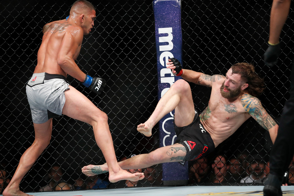 . Anthony Pettis knocks down Michael Chiesa in a lightweight mixed martial arts bout at UFC 226, Saturday, July 7, 2018, in Las Vegas. (AP Photo/John Locher)