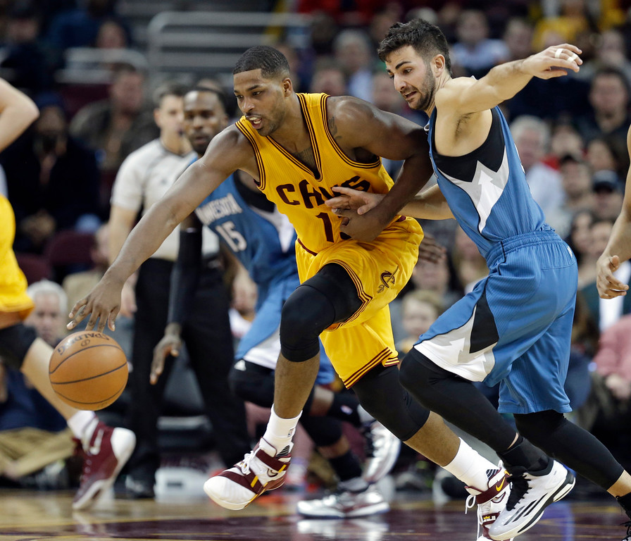. Cleveland Cavaliers\' Tristan Thompson, left, from Canada, and Minnesota Timberwolves\' Ricky Rubio, from Spain, battle for a loose ball in the second half of an NBA basketball game Monday, Jan. 25, 2016, in Cleveland. The Cavaliers won 114-107. (AP Photo/Tony Dejak)