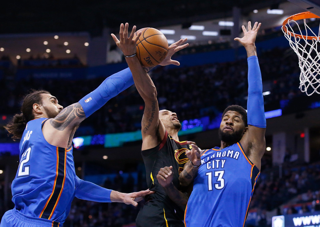 . Oklahoma City Thunder center Steven Adams, left, knocks the ball away from Cleveland Cavaliers guard George Hill, center, as Hill shoots in front of forward Paul George (13) during the first half of an NBA basketball game in Oklahoma City, Tuesday, Feb. 13, 2018. (AP Photo/Sue Ogrocki)