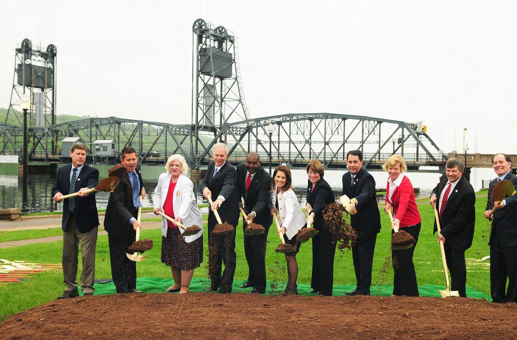 . Officials pose with a ceremonial shovel-full of dirt at the groundbreaking ceremony.  From left: U.S. Rep. Ron Kind and U.S. Rep. Sean Duffy from Wisconsin; Oak Park Heights, Minn., Mayor Mary McComber; U.S. Sen. Ron Johnson of Wisconsin; Federal Highway Administration Division Administrator Derrell Turner;  U.S. Rep. Michele Bachman, Minnesota; U.S. Sen. Amy Klobuchar,  Minnesota; Wisconsin Gov. Scott Walker;  U.S. Sen. Tammy Baldwin, Wis.; Stillwater Mayor Ken Harycki; and Minnesota Department of Transportation Commissioner Charlie Zelle. (Pioneer Press: Scott Takushi)
