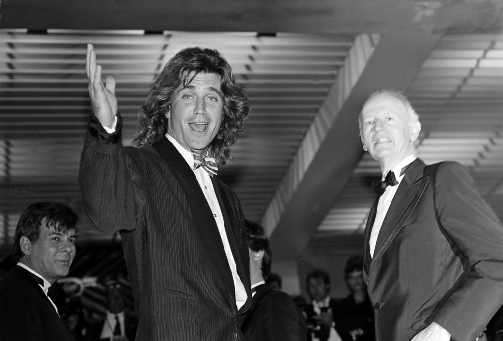 . Australian actor Mel Gibson, left, waves as he arrives for a viewing oat the palace at the 4oth Cannes Film Festival in Cannes, France,  late Sunday night, May 11, 1987.   (AP Photo/Gilbert Tourte)