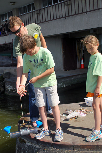 "Since boat rides were ""first come, first served,"" we kept plenty of things on the Hasler Lab dock for visitors to try out. Here, Luke Winslow helps a young visitor take a water sample with a Van Dorn trap."