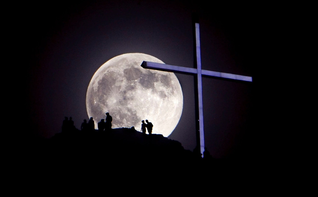 ". A ""super moon\"" rises over Table Rock and the lighted cross near Boise, Idaho on Saturday night, June 22, 2013.   The larger than normal moon called a \""super moon\"" happens only once this year as the moon on its elliptical orbit is at its closest point to earth and appears 13.5 percent larger than usual.  (AP Photo/The Idaho Statesman, Kyle Green)"