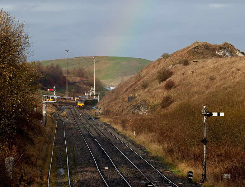 EWS 60011 with rock train and a faint rainbow in Peak Forest South.