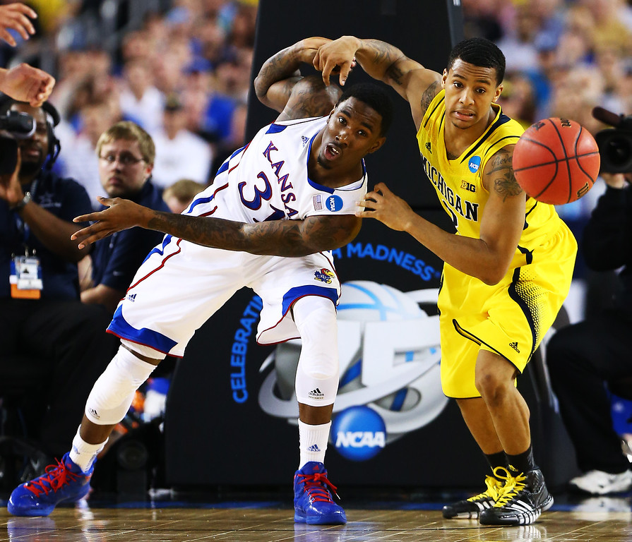 . ARLINGTON, TX - MARCH 29:  Jamari Traylor #31 of the Kansas Jayhawks and Trey Burke #3 of the Michigan Wolverines vie for a looseball in the second half during the South Regional Semifinal round of the 2013 NCAA Men\'s Basketball Tournament at Dallas Cowboys Stadium on March 29, 2013 in Arlington, Texas.  (Photo by Tom Pennington/Getty Images)