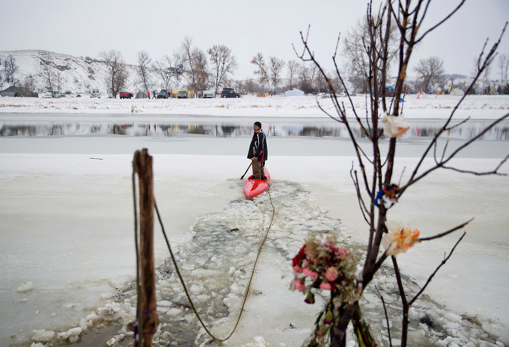 . In this Thursday, Dec. 1, 2016 photo, a man breaks through the ice to build a path for incoming canoes carrying travelers down the Cannonball river at the Oceti Sakowin camp where people have gathered to protest the Dakota Access oil pipeline in Cannon Ball, N.D. So far, those at the camp have shrugged off the heavy snow, icy winds and frigid temperatures. But if they defy next week\'s government deadline to abandon the camp, demonstrators know the real deep freeze lies ahead. Life-threatening wind chills and towering snow drifts could mean the greatest challenge is simple survival. (AP Photo/David Goldman)