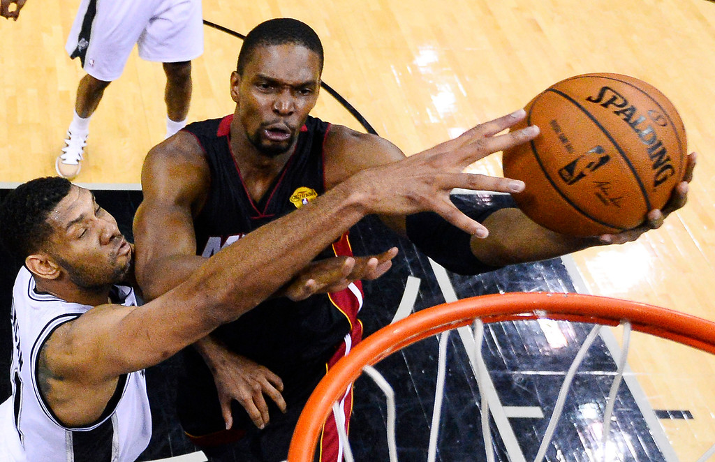 . Miami Heat center Chris Bosh shoots as San Antonio Spurs forward Tim Duncan, left, defends during the first half in Game 2 of the NBA basketball finals on Saturday, Nov. 8, 2014, in San Antonio. (AP Photo/Larry W. Smith, pool)