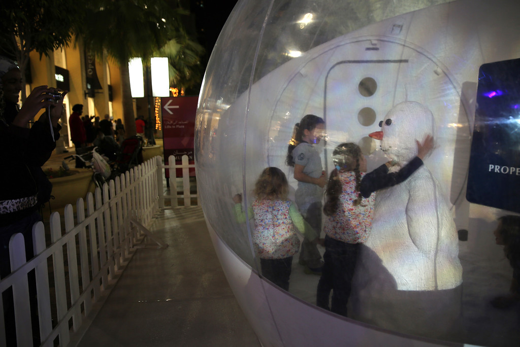 . Girls play with a snowman inside a plastic ball covered with artificial snow at the Jumeirah Beach Residence, JBR Walk in Dubai, United Arab Emirates on Christmas day, Wednesday Dec. 25, 2013. (AP Photo/Kamran Jebreili)
