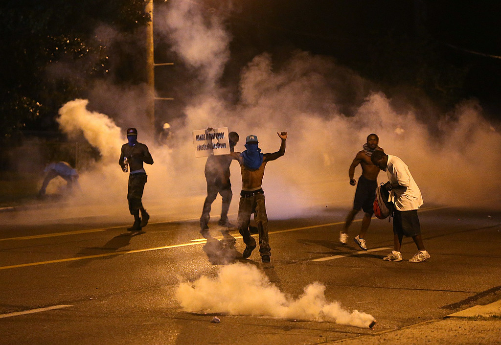 . People protest as tear gas canisters detonate around them on Wednesday, Aug. 13, 2014, in Ferguson, Mo. Protests in the St. Louis suburb rocked by racial unrest since a white police officer shot an unarmed black teenager to death turned violent Wednesday night, with people lobbing molotov cocktails at police who responded with smoke bombs and tear gas to disperse the crowd. (AP Photo/St. Louis Post-Dispatch, Chris Lee)