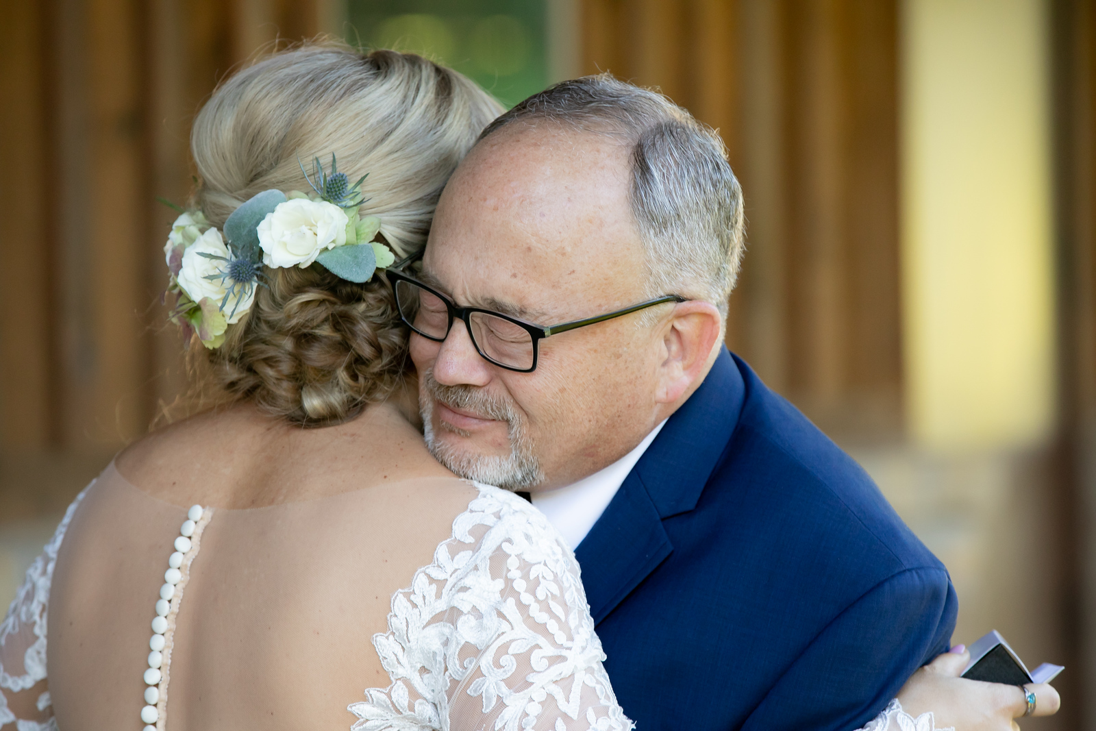 a bride hugging her father just before her wedding ceremony
