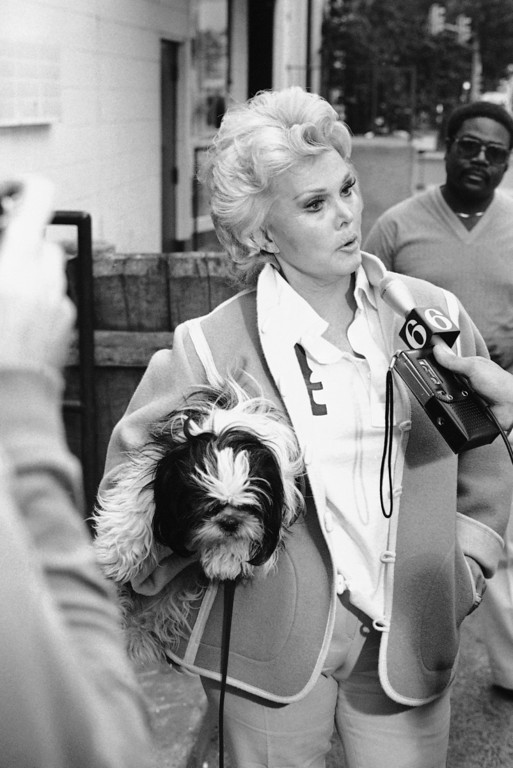 . Zsa Zsa Gabor holds her dog while talking with a member of the news media as she arrives at Philadelphia\'s City Line dinner theater on Thursday, June 2, 1983 for her performance.     (AP Photo/Frank Freudberg)