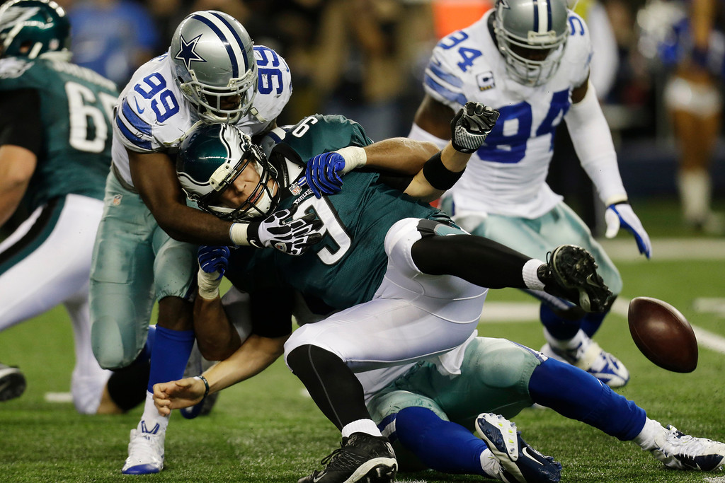 . Philadelphia Eagles quarterback Nick Foles (9) fumbles the ball as he is sacked by Dallas Cowboys defensive tackle Jason Hatcher (97) as defensive end George Selvie (99) helps during the second half of an NFL football game, Sunday, Dec. 29, 2013, in Arlington, Texas. (AP Photo/Tim Sharp)