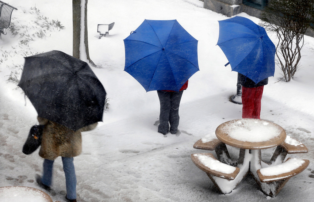 . People stand together in a snowfall in Trenton, N.J., Friday, March 8, 2013. (AP Photo/Mel Evans)