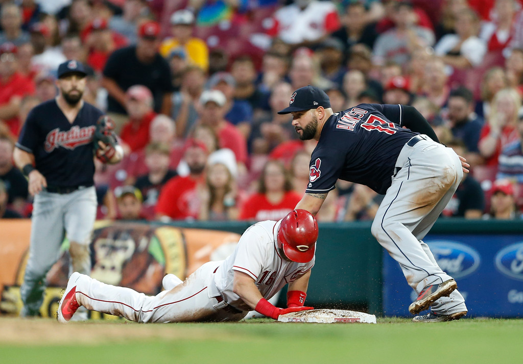 . Cincinnati Reds\' Tucker Barnhart is safe at first with a bunt single as Cleveland Indians first baseman Yonder Alonso (17) attempts the tag during the third inning of a baseball game Wednesday, Aug. 15, 2018, in Cincinnati. (AP Photo/Gary Landers)