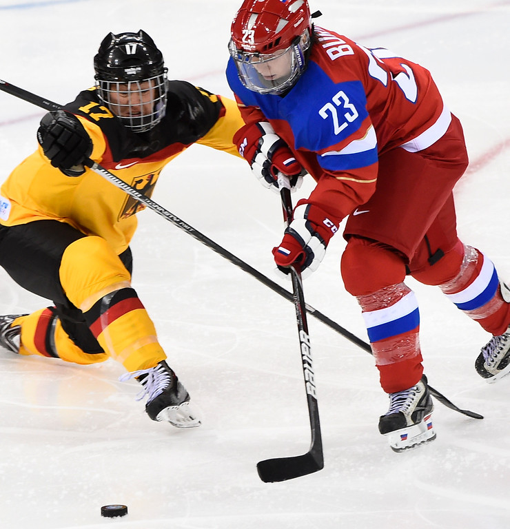 . Russia\'s Tatyana Burina (R) vies with Germany\'s Sara Seiler during a Women\'s Ice Hockey Group B match between Russia and Germany at the Shayba Arena during the Sochi Winter Olympics on February 9, 2014. JONATHAN NACKSTRAND/AFP/Getty Images