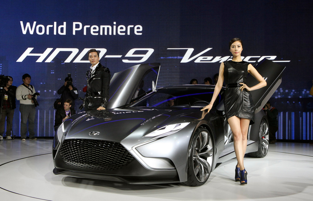 . South Korean models pose with a Hyundai Motors\' HND-9 Venace during a press day of the Seoul Motor Show in Goyang, South Korea, Thursday, March 28, 2013. The exhibition will be held from March 29 to April 7 and will feature 384 companies from 14 countries. (AP Photo/Ahn Young-joon)