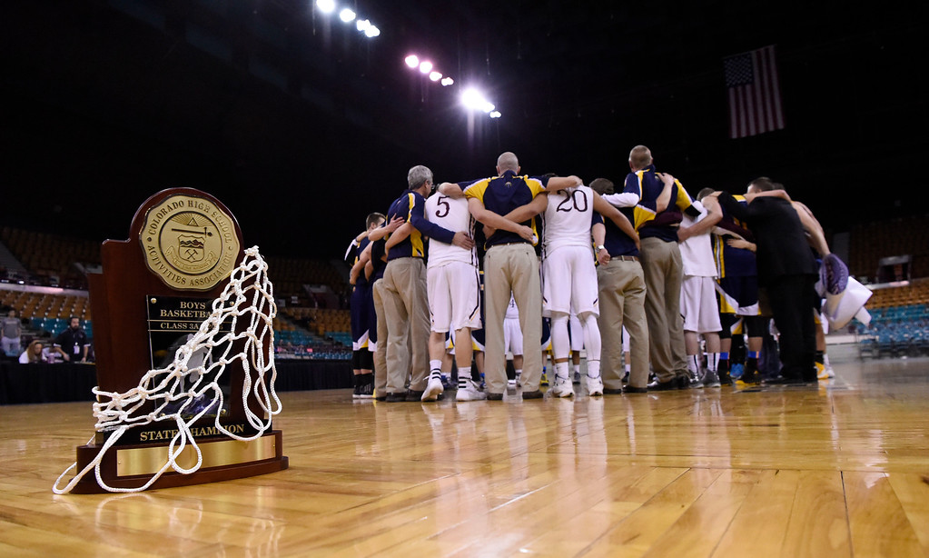 . CS Christian Lions put their championship trophy to the side as they say prayer with Alamos Mean Mmoose after the Championship 3A game at the Coliseum.  Christian defeated Alamos 57-43 for back to back championships. (Photo By John Leyba/The Denver Post)