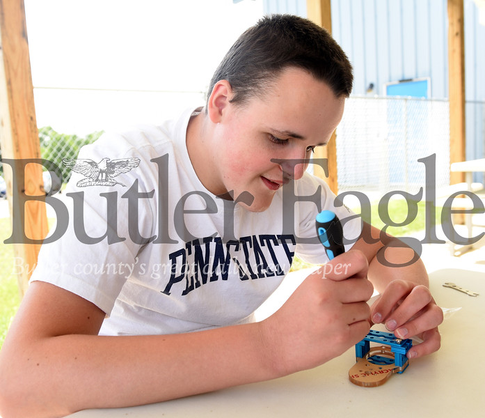 Harold Aughton/Butler Eagle: Ryan Rumbaugh works on assembling a robot with fellow campers at Community Connections, Tuesday, June 25.