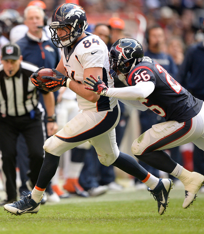 . Denver Broncos tight end Jacob Tamme (84) catches a pass for a first down as Houston Texans defensive back Brandon Harris (26) shoves him out of bounds during the fourth quarter December 22, 2013 at Reliant Stadium. (Photo by John Leyba/The Denver Post)