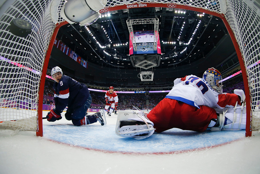 . The puck hits the back of the net past Russia goaltender Sergei Bobrovski as USA forward Zach Parise looks on in the third period of a men\'s ice hockey game at the 2014 Winter Olympics, Saturday, Feb. 15, 2014, in Sochi, Russia. The USA won 3-2 in an overtime shootout. (AP Photo/Julio Cortez, Pool)