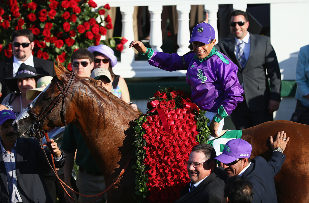 Description of . Victor Espinoza celebrates  in the winners circle after riding California Chrome #5 to victory in the 140th running of the Kentucky Derby at Churchill Downs on May 3, 2014 in Louisville, Kentucky.  (Photo by Andy Lyons/Getty Images)