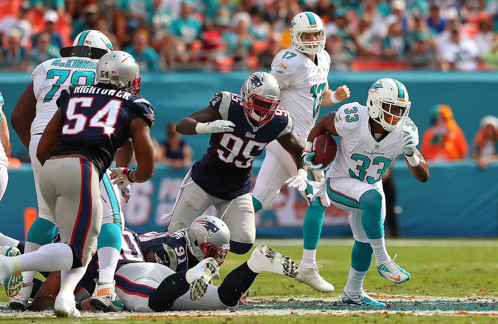 . Daniel Thomas #33 of the Miami Dolphins rushes during a game against the New England Patriots at Sun Life Stadium on December 15, 2013 in Miami Gardens, Florida.  (Photo by Mike Ehrmann/Getty Images)