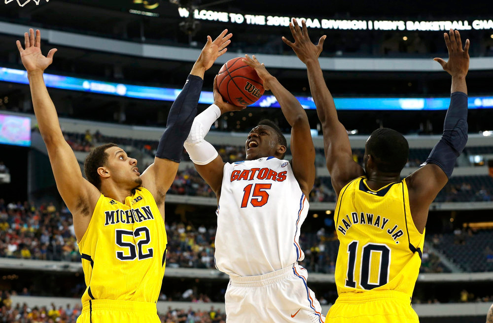 . Florida Gators forward Will Yeguete (C) is guarded by Michigan Wolverines forward Jordan Morgan (L) and guard Tim Hardaway Jr. in their South Regional NCAA men\'s basketball game in Arlington, Texas March 31, 2013. REUTERS/Jim Young