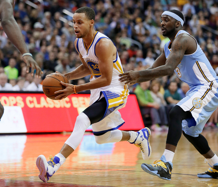 . Golden State Warriors guard Stephen Curry, left, drives past Denver Nuggets guard Ty Lawson during the first half of a preseason NBA basketball game, Thursday, Oct. 16, 2014, in Des Moines, Iowa. (AP Photo/Charlie Neibergall)
