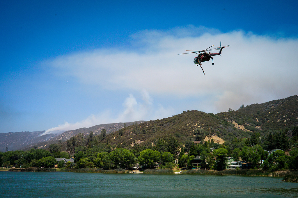 . A water dropping helicopter picks up water from Lake Huges to drop on the Power House fire which continued to burn in an area mort of Santa Clarita Monday.   Photo by David Crane/Los Angeles Daily News